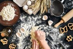 As mãos do ` s da mulher amassam a massa na tabela com farinha, ovos e ingredientes Vista superior Imagem de Stock