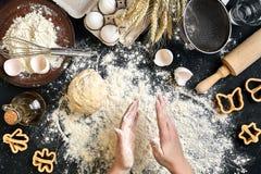 As mãos do ` s da mulher amassam a massa na tabela com farinha, ovos e ingredientes Vista superior Imagens de Stock