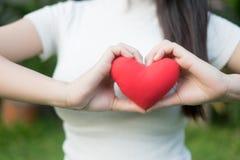 As mãos do ` s da mulher com tratamento de mãos exato bonito mantêm com cuidado o coração vermelho fotos de stock royalty free