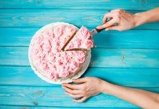 As mãos do ` s da mulher cortaram o bolo com creme cor-de-rosa no fundo de madeira azul Bolo cor-de-rosa Imagem de Stock Royalty Free