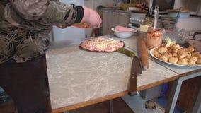 As mãos do ` s da mulher cortaram o pepino posto de conserva nas fatias, preparando a pizza filme