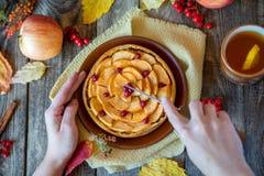 As mãos do ` s da mulher cortaram a torta de Apple em uma textura de madeira Imagem de Stock Royalty Free