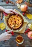 As mãos do ` s da mulher cortaram a torta de Apple em uma textura de madeira Foto de Stock Royalty Free