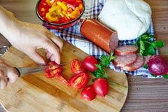 As mãos do ` s da mulher cortaram um tomate Imagem de Stock Royalty Free