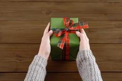 As mãos do ` s da mulher dão o presente do Natal na caixa atual Imagem de Stock