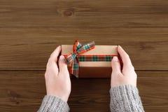 As mãos do ` s da mulher dão o presente do Natal na caixa atual Fotos de Stock