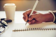 As mãos do ` s da mulher estão escrevendo o copo da nota e de café no spect aberto Foto de Stock
