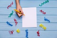 As mãos do ` s da mulher guardam a pena e a escrita no papel vazio branco com fitas coloridas ao redor Imagens de Stock