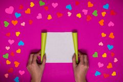 As mãos do ` s da mulher guardam a placa do papel no fundo cor-de-rosa Imagem de Stock