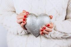 As mãos do ` s da mulher mantêm com cuidado o coração de prata imagens de stock