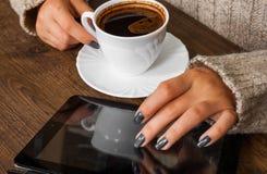 As mãos do ` s da mulher na camiseta que guarda a xícara de café e os usos anulam o dispositivo da tabuleta Imagem de Stock Royalty Free