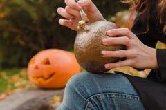 As mãos do ` s da mulher tiram na abóbora de Dia das Bruxas Foto de Stock Royalty Free