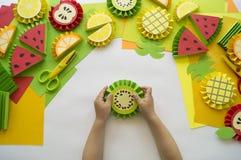 As mãos do ` s das crianças fazem o fruto do papel verão dos trópicos Classe mestra da criança imagens de stock royalty free