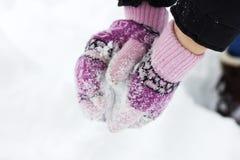 As mãos do ` s das mulheres em mitenes roxos fazem uma bola de neve Imagem de Stock