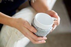 As mãos do ` s das mulheres guardam um copo da bebida em suas mãos Foto de Stock