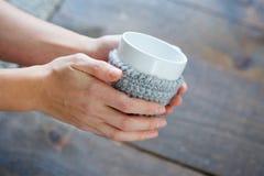 As mãos do ` s das mulheres guardam um copo da bebida em suas mãos Fotografia de Stock Royalty Free