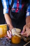 As mãos do ` s das mulheres guardam um frasco do mel Foto de Stock Royalty Free