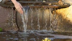 As mãos do ` s das mulheres tocam na água transparente que flui abaixo das pedras, movimento lento vídeos de arquivo