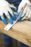 As mãos do ` s do carpinteiro em luvas protetoras indicam com um lápis a dimensão com um ângulo Fotos de Stock Royalty Free