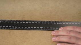As mãos do ` s do homem tiram uma linha do lápis em uma régua video estoque