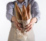 As mãos do ` s do padeiro guardam o pão fresco Fotos de Stock