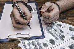 As mãos do ` s dos homens com algemas enchem o registro da polícia, confissão imagens de stock