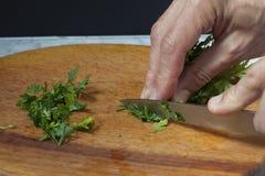 As mãos do ` s dos homens cortaram a salsa com uma faca em uma placa de corte Imagens de Stock Royalty Free