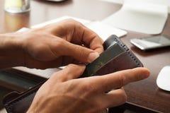 As mãos do ` s dos homens obtêm um cartão de crédito de sua carteira Fotografia de Stock Royalty Free