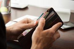 As mãos do ` s dos homens obtêm um cartão de crédito de sua carteira Fotos de Stock Royalty Free