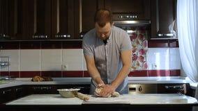As mãos do ` s dos homens preparam a massa da pizza na tabela na cozinha video estoque