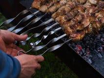 As mãos do ` s dos homens viram espetos com a carne roasted foto de stock