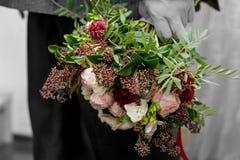 As mãos do ` s do homem com um ramalhete do noivo do flowersthe guardam um ramalhete do casamento no homem do bouqueta do casamen fotografia de stock