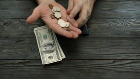 As mãos do ` s do homem contam os dólares americanos e centavos, cédulas e moedas de uma bolsa de couro preta video estoque