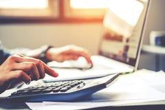 As mãos do ` s do homem de negócios com a calculadora no escritório e nos dados financeiros custaram econômico imagens de stock