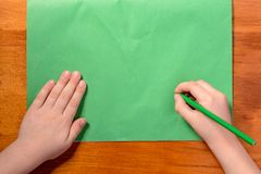 As mãos do ` s do menino guardam um lápis verde na perspectiva do papel verde foto de stock royalty free