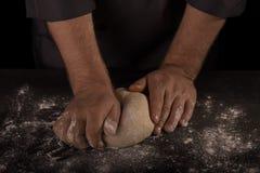 As mãos do ` s do padeiro amassam a massa para o pão, isolada no preto imagens de stock