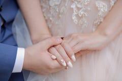 As mãos do tema do casamento dos recém-casados que guarda recém-casados das mãos imagem de stock