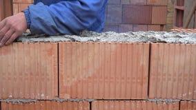 As mãos do trabalhador aplicam o almofariz, arranjam tijolos na parede de alvenaria, casa da construção video estoque