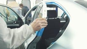 As mãos do trabalhador cobrem o carro antes de pintar - pintor profissional do carro na oficina do veículo vídeos de arquivo