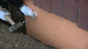 As mãos do trabalhador com martelo e plástico ancoram o painel do poliestireno da fixação vídeos de arquivo