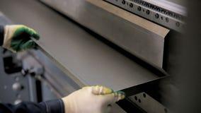 As mãos do trabalhador dobram a folha de metal em uma máquina industrial de dobra moderna em uma fábrica filme