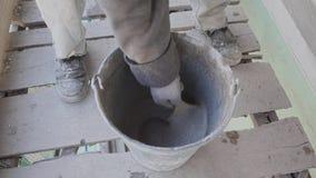 As mãos do trabalhador estão misturando a massa concreta molhada com a escova de pintura na cubeta video estoque