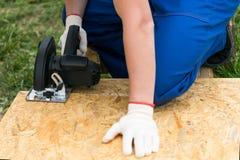 As mãos do trabalhador guardam uma serra circular para cortar um protetor de madeira fotografia de stock