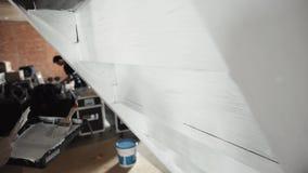 As mãos do trabalhador masculino pintam ativamente paredes cinzentas no branco com escova grande filme