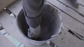 As mãos do trabalhador removem exatamente a massa concreta molhada com a escova de pintura da cubeta vídeos de arquivo