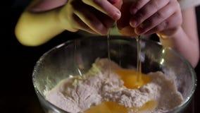 As mãos do ` um s da criança racham um ovo filme