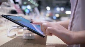 As mãos dos compradores usam o tablet pc moderno com o tela táctil na loja da eletrônica no fundo borrado, close-up video estoque