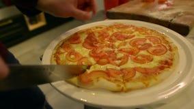 As mãos dos homens cortaram com uma pizza quente da faca video estoque
