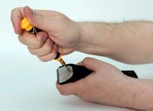 As mãos dos homens destorcem os parafusos com uma tosquiadeira da lâmina de chave de fenda o cabelo foto de stock