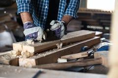 As mãos dos homens do close-up nas luvas com a plaina seguram a placa de madeira, trabalho manual, diy, trabalhos imagem de stock